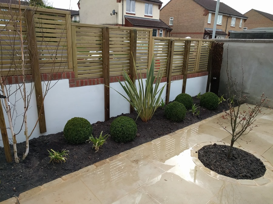 solid wall with laterally slatted fence on top
