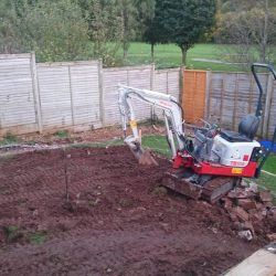 contouring a sloping garden using a mini digger and retaining walls