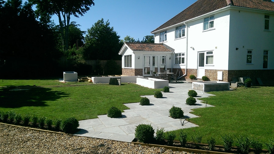 Contemporary garden with contrasting paths, lawns and buxus balls