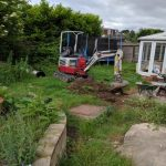 early stages of garden landscaping with mini digger clearing site