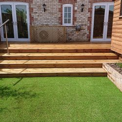 timber deck with steps leading down to artificial grass