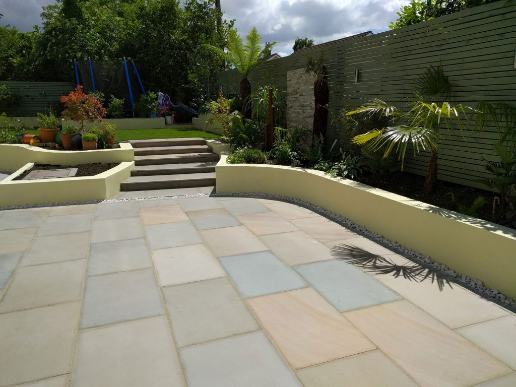 beautiful garden with large patio and steps leading to lawns