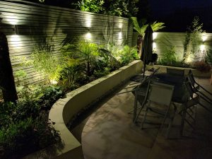 twighlight garden with planting accentuated by garden lighting