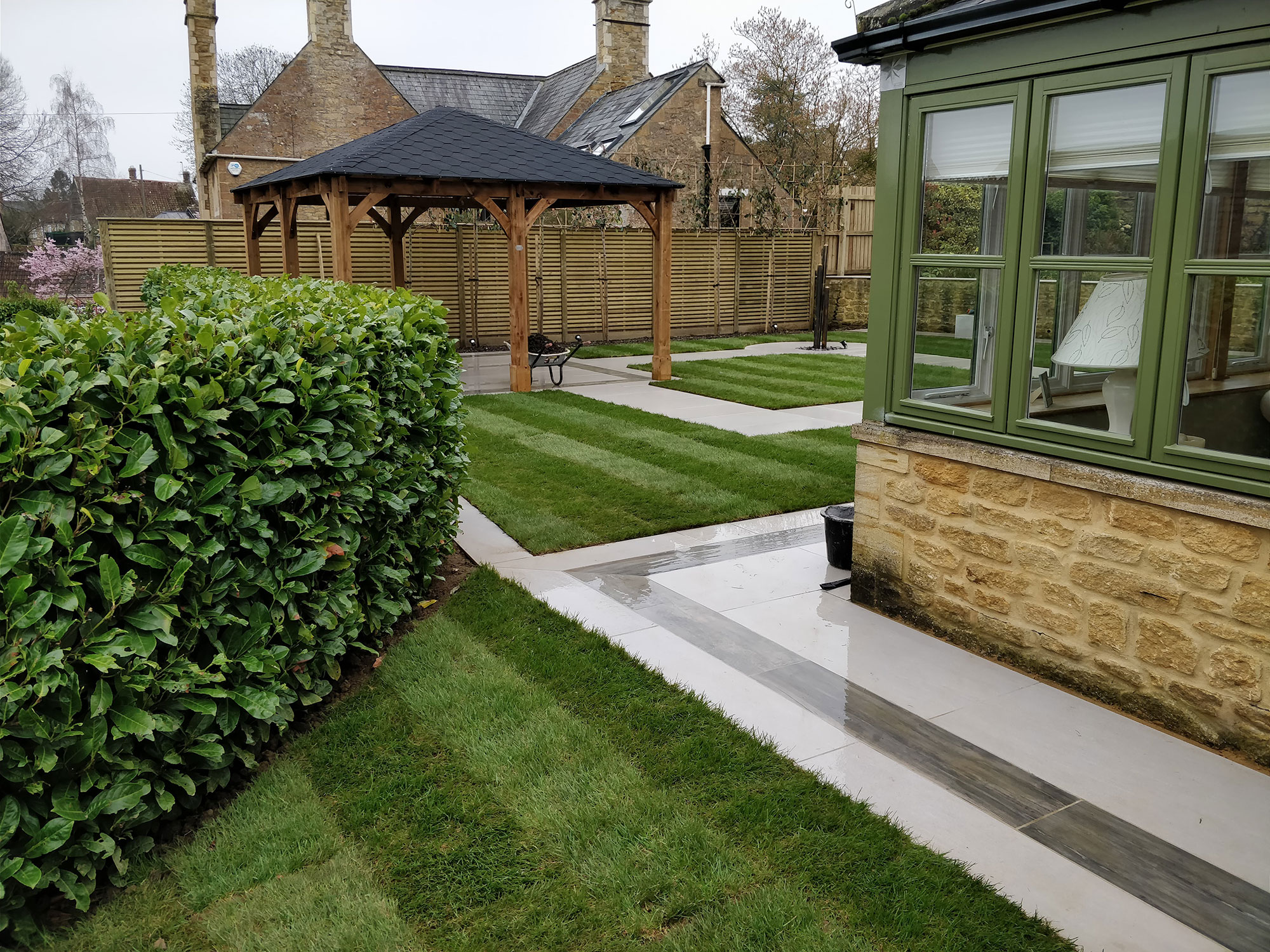 porcelain paved patios with turfed lawns in a contemporary garden