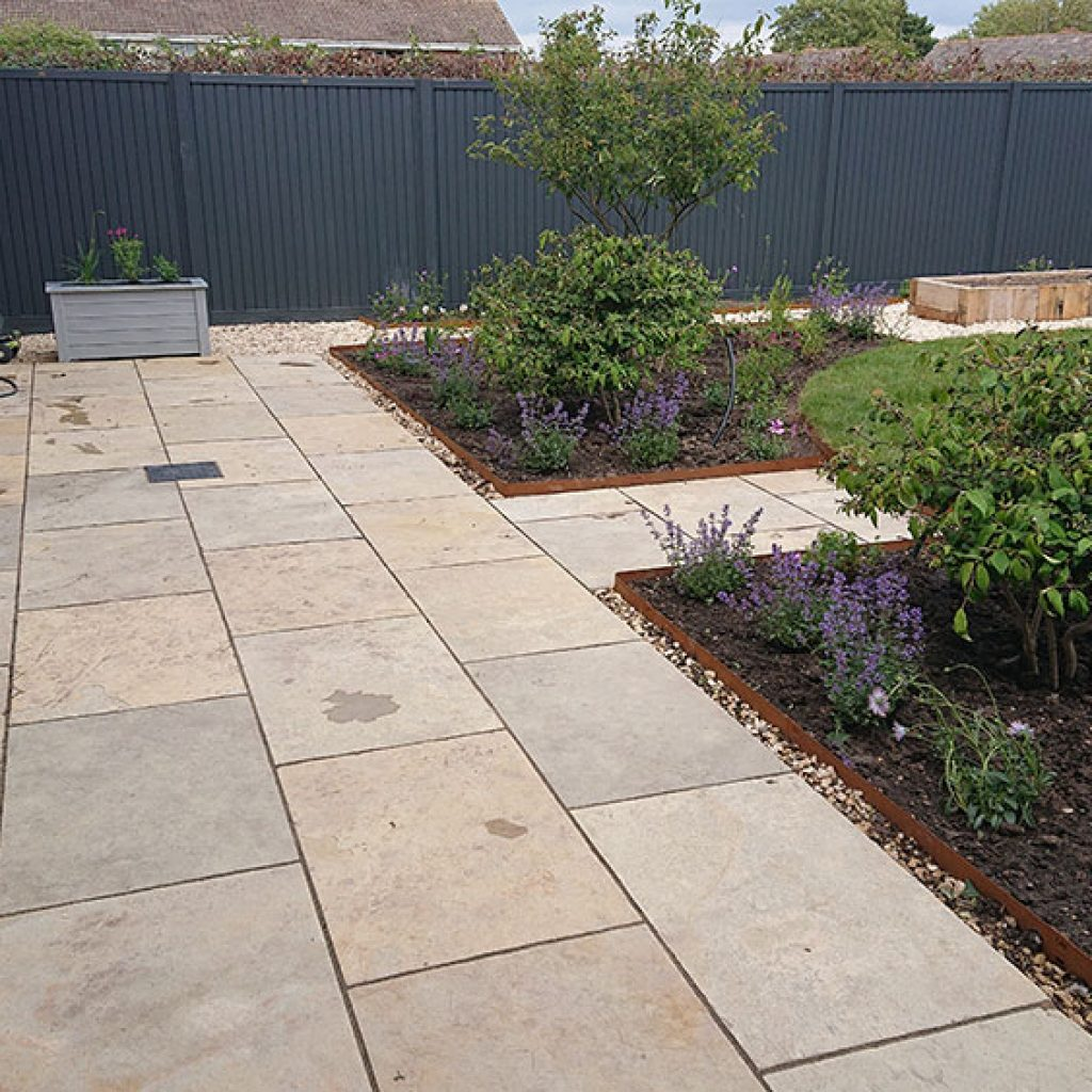 newly landscaped back garden with modern patio and country style planting