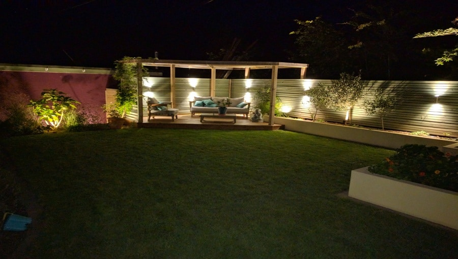 professionally built garden with timber structures and evening lighting