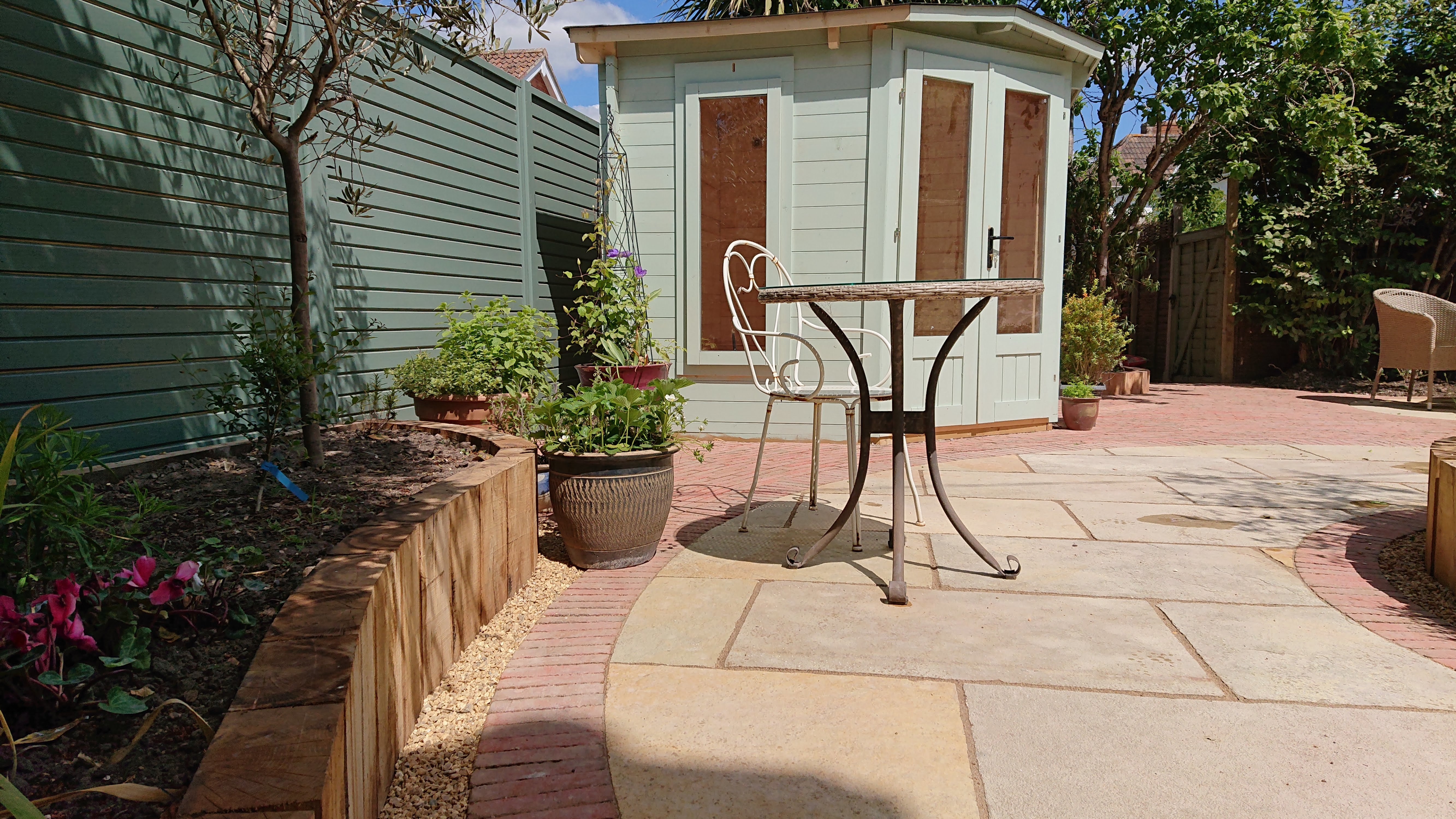pretty summerhouse with paved area and raised timber beds